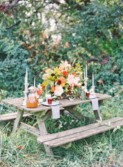Flower arrangement and place setting on a picnic table