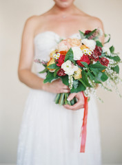Bridal bouquet with dress in the background