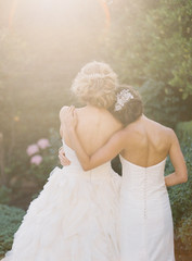 Bridesmaid with arm around bride