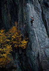 Woman rock climbing up rockface