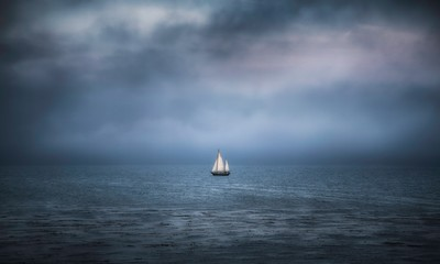 Sailboat on ocean under storm clouds
