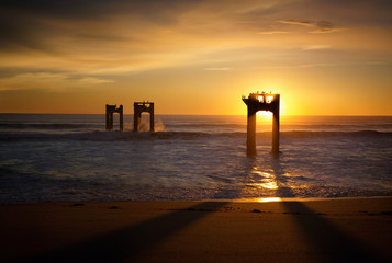 Silhouette of dilapidated pier supports in ocean at sunset