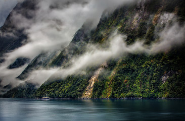 Boat on lake by misty lush green mountainside