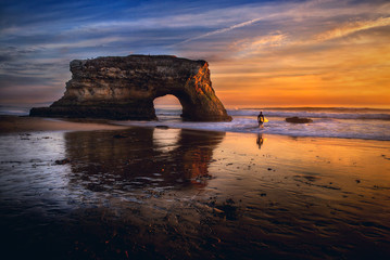 Surfer carrying surfboard into ocean by rock formation at sunset