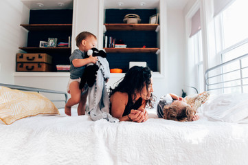 Mother and children on bed together