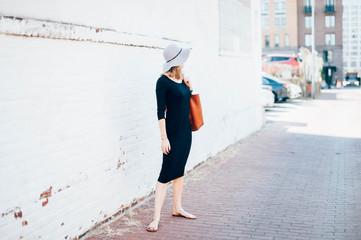 Woman in street wearing sunhat looking away