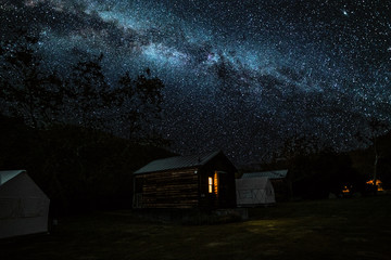 Log cabin and tent under starry sky