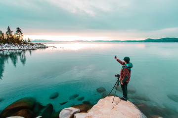 Man by lake Tahoe using smartphone to take photograph