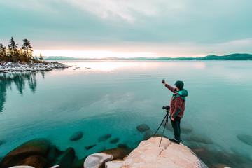 Man by lake Tahoe using smartphone to take photograph