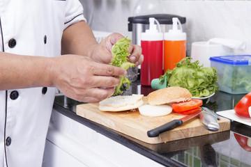 Chef prepared slice of lettuce on the Hamburger bun