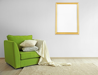 Green armchair and picture frame on light wall background