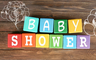 Colorful cubes on wooden background. Baby shower concept