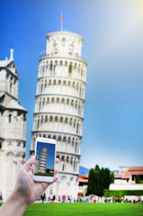 Blur Pisa tower with blue sky and capture Pisa tower by smart phone in hand holding of traveler.