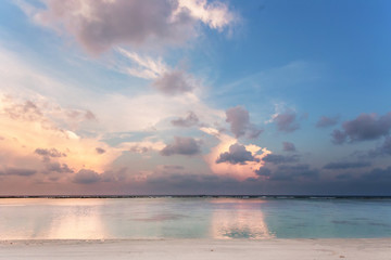 Beach on dusk, after sunset  with white sand and blue and white water