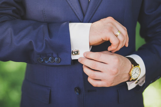 Man in suit. Mail dress fashion. Close up of man hands and sleeves of blue suit and white shirt. Groom, businessman or groomsman.