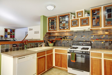 Bright kitchen interior with brown tile and colourful cabinets with stained glass doors