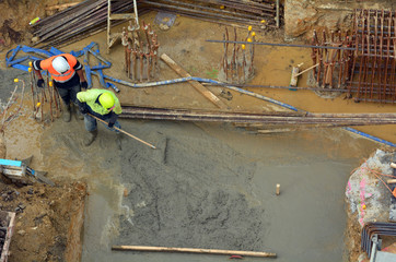 Builders levelling cement in building site