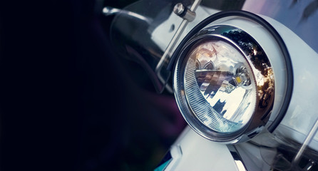 Colorful headlight of scooter on dark background