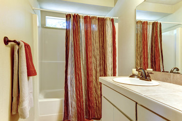 Simple bathroom with red and browns colors in shower curtain and