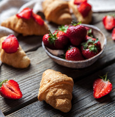 A delicious breakfast of strawberries and bread on wooden background. Fruit, food, sandwiches, cheese. Vintage style.