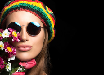 Pretty hippie girl in sunglasses with flowers