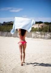 bella ragazza che corre di spalle  in costume sulla spiaggia