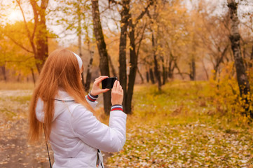 The girl photographs the mobile phone in autumn park. In hands the mobile phone.