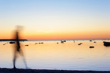 Man defocused silhouette walking on seaside at sunset