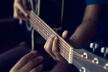 Female hands learning to play  acoustic guitar