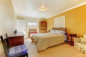 Nice yellow bedroom interior with carved wood bed, nightstand an