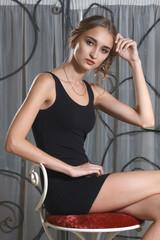 pretty girl in short black dress sitting
