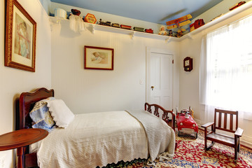 Bright white boys room with wood bed, rocking chair  and coloufu
