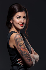 Beautiful tattoed young woman standing with hands folded