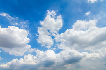 The background bright blue sky with clouds