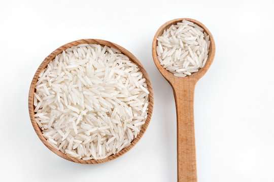 Rice in wooden spoon and bowl on white background.  Top view, high resolution product.