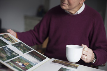 Senior Man Looking Through Photo Album At Home