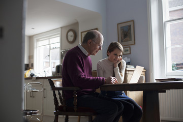 Granddaughter Helping Grandfather To Use Laptop Computer