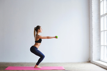 Beautiful woman exercises with dumbbells.