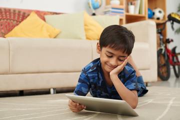 Smiling Asian boy watching cartoon on digital tablet