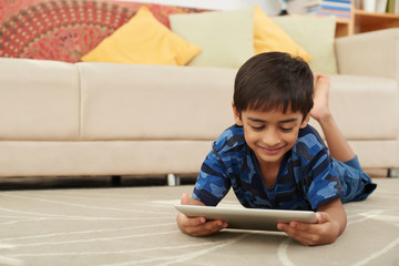 Smiling boy lying on floor and watching movie on tablet