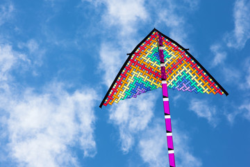 Rainbow colored kite flying high against sunny blue skies for Summer and vacation concept.