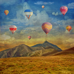 Grunge image  of colorful hot air balloons against  sky