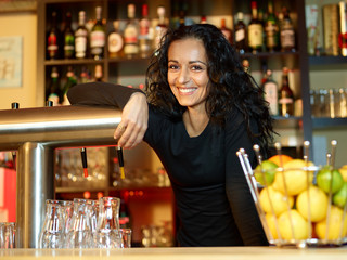 Woman bartender with a glass of beer at work