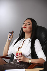 Portrait of a relaxed young businesswoman sitting with legs on d