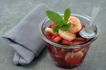 Dessert avec un mélange de fraises et de rondelles de bananes et feuilles de menthe