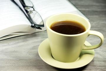 Kaffeetasse, Lesebrille und ein Buch