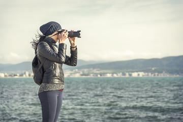 Girl photographer takes photos or videos near the sea.