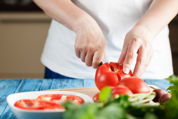 Closeup Of Young Woman In Kitchen Cutting Vegetables