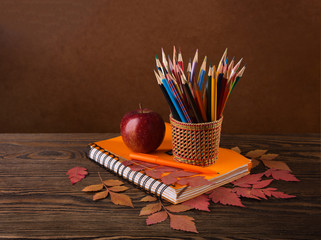 Colorful pencils, apple  and  dry autumn leaves  on wooden table.