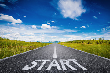 start text on long road with green field and blue sky